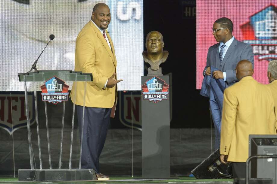 Former Seattle Seahawks tackle Walter Jones, left, unveils his bust with his son Walterius Jones, right, during the NFL Class of 2014 Pro Football Hall of Fame Enshrinement Ceremony at Fawcett Stadium on August 2, 2014 in Canton, Ohio. Photo: Jason Miller, Getty Images
