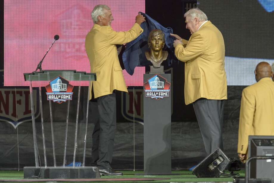 Former NFL punter Ray Guy, left, unveils his bust with his former head coach John Madden, right, during the NFL Class of 2014 Pro Football Hall of Fame Enshrinement Ceremony at Fawcett Stadium on August 2, 2014 in Canton, Ohio. Photo: Jason Miller, Getty Images