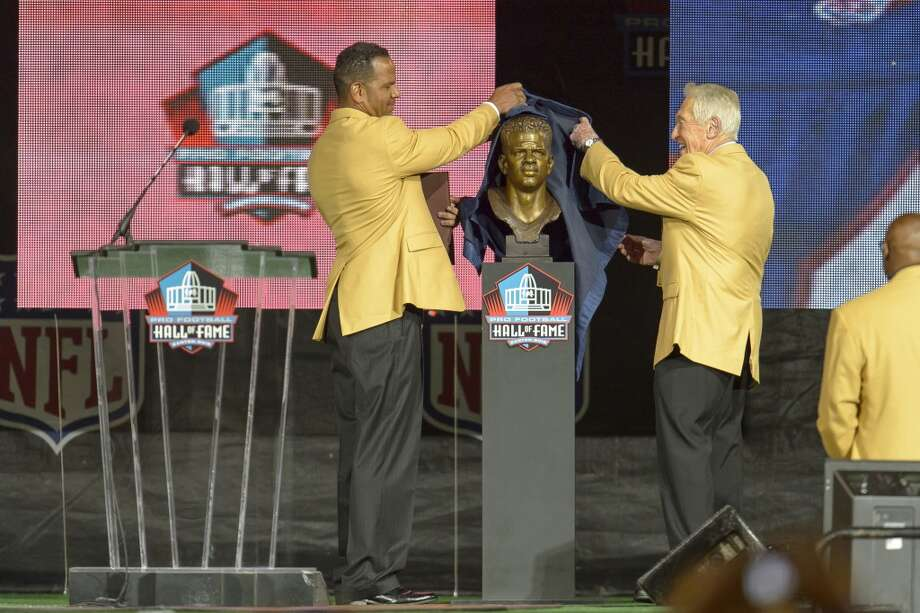 Former NFL wide receiver Andre Reed, left, unveils his bust with his former coach Marv Levy, right, during the NFL Class of 2014 Pro Football Hall of Fame Enshrinement Ceremony at Fawcett Stadium on August 2, 2014 in Canton, Ohio. Photo: Jason Miller, Getty Images