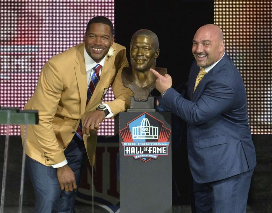 Inductee Michael Strahan, left, poses next to his bronze bust with presenter Jay Glazer during the Pro Football Hall of Fame enshrinement ceremony Saturday, Aug. 2, 2014, in Canton, Ohio. Photo: David Richard, Associated Press