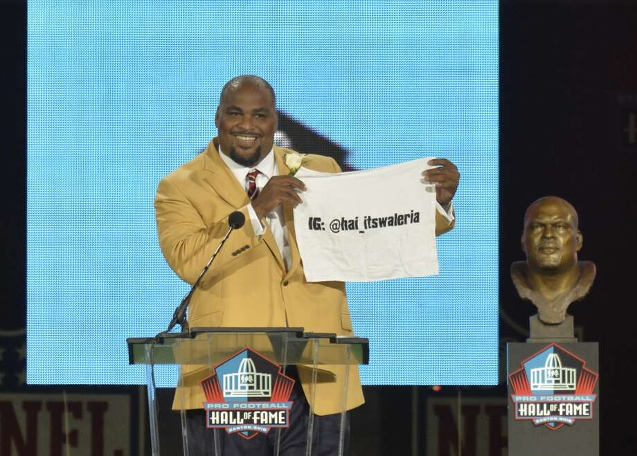 Hall of Fame inductee Walter Jones holds up a towel with his daughter's Instagram address during the Pro Football Hall of Fame enshrinement ceremony Saturday, Aug. 2, 2014, in Canton, Ohio. Photo: David Richard, Associated Press