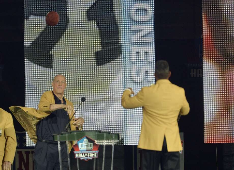 Former Buffalo Bills quarterback Jim Kelly, left, throws a pass to Hall of Fame inductee Andre Reed during the Pro Football Hall of Fame enshrinement ceremony Saturday, Aug. 2, 2014, in Canton, Ohio. Photo: David Richard, Associated Press