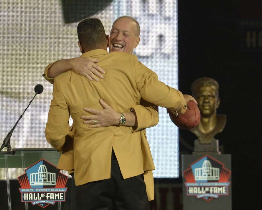 Former Buffalo Bills quarterback Jim Kelly, back, hugs inductee Andre Reed during the Pro Football Hall of Fame enshrinement ceremony Saturday, Aug. 2, 2014, in Canton, Ohio. Photo: David Richard, Associated Press