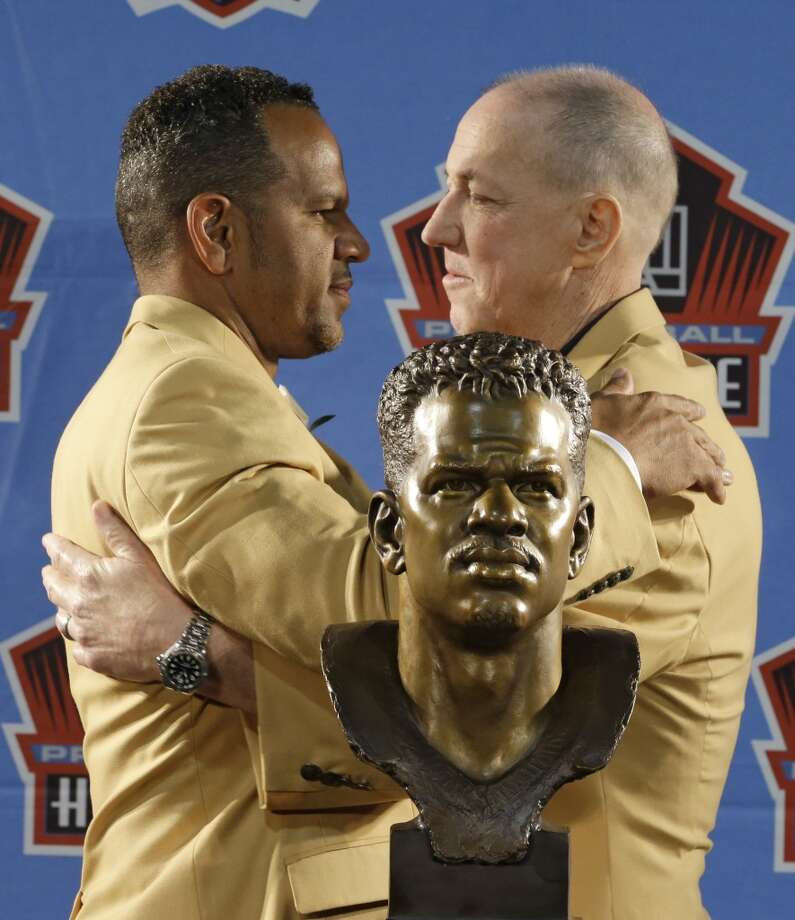 Hall of Fame inductee Andre Reed, left, and former Buffalo Bills quarterback Jim Kelly hug during the Pro Football Hall of Fame enshrinement ceremony Saturday, Aug. 2, 2014, in Canton, Ohio. Photo: Tony Dejak, Associated Press