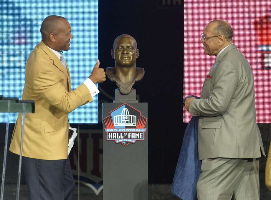 Hall of Fame inductee Aeneas Williams, left, and his father and presenter, Lawrence Williams, react after uncovering his bronze bust during the Pro Football Hall of Fame enshrinement ceremony Saturday, Aug 2, 2014, in Canton, Ohio. Photo: David Richard, Associated Press
