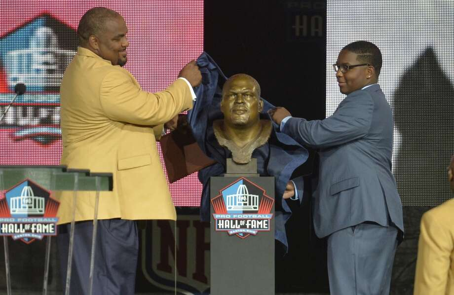 Hall of Fame inductee Walter Jones, left, and his son and presenter, Walterius Jones, uncover his bronze bust during the Pro Football Hall of Fame enshrinement ceremony Saturday, Aug 2, 2014 in Canton, Ohio. Photo: David Richard, Associated Press