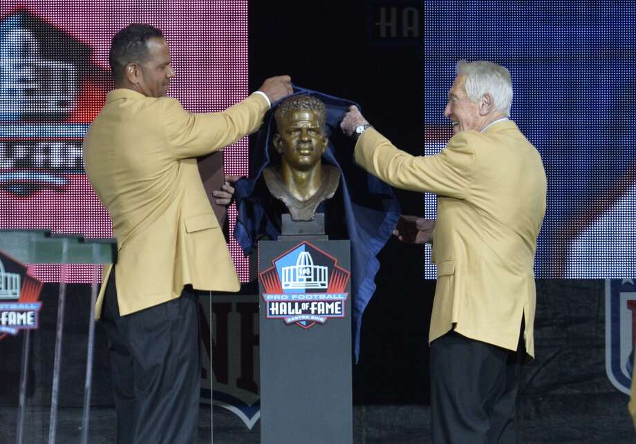 Hall of Fame inductee Andre Reed, left, uncovers his bronze bust with presenter Marv Levy during the Pro Football Hall of Fame enshrinement ceremony Saturday, Aug. 2, 2014, in Canton, Ohio. Photo: David Richard, Associated Press