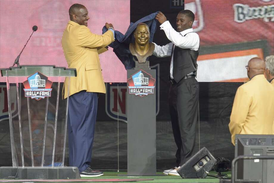 Former Tampa Buccaneers linebacker Derrick Brooks, left, unveils his bust with his son Decalon Brooks, right, during the NFL Class of 2014 Pro Football Hall of Fame Enshrinement Ceremony at Fawcett Stadium on August 2, 2014 in Canton, Ohio. Photo: Jason Miller, Getty Images