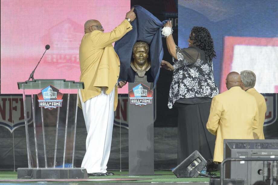 Former NFL defensive end Claude Humphrey, left, unveils his bust with his daughter Cheyenne Humphrey-Robinson, right, during the NFL Class of 2014 Pro Football Hall of Fame Enshrinement Ceremony at Fawcett Stadium on August 2, 2014 in Canton, Ohio. Photo: Jason Miller, Getty Images