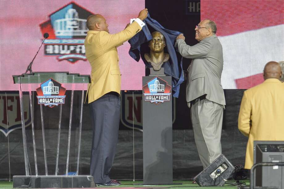 Former NFL cornerback/safety Aeneas Williams, left, unveils his bust with his father Lawrence Williams, right, during the NFL Class of 2014 Pro Football Hall of Fame Enshrinement Ceremony at Fawcett Stadium on August 2, 2014 in Canton, Ohio. Photo: Jason Miller, Getty Images