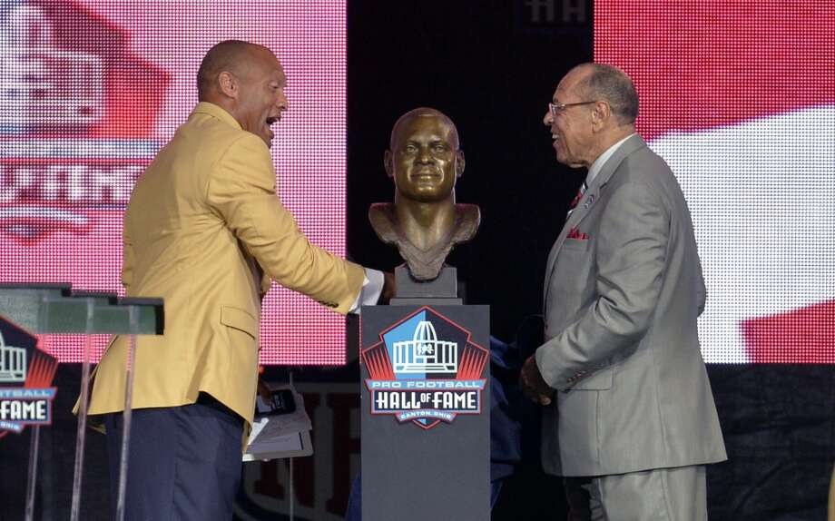 Hall of Fame inductee Aeneas Williams, left, and his father and presenter Lawrence Williams, uncover his bronze bust during the 2014 Pro Football Hall of Fame Enshrinement Ceremony at the Pro Football Hall of Fame Saturday, Aug 2, 2014 in Canton, Ohio. Photo: David Richard, Associated Press