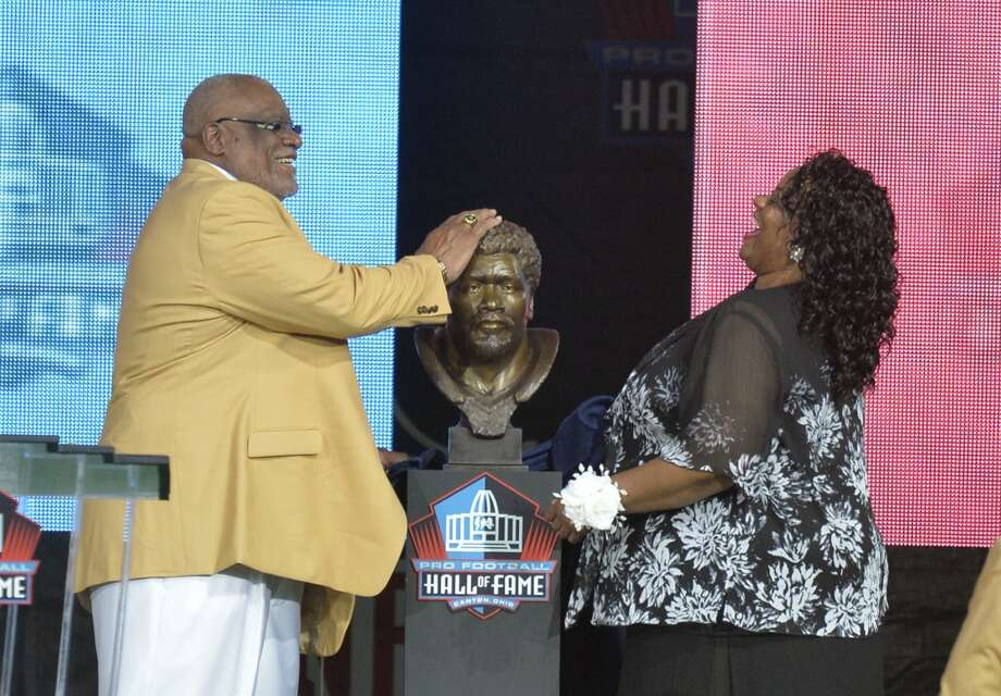 Hall of Fame inductee Claude Humphrey, left, touches his bronze bust beside his daughter, presenter Cheyenne Humphrey-Robinson, during the Pro Football Hall of Fame enshrinement ceremony Saturday, Aug 2, 2014, in Canton, Ohio. Photo: David Richard, Associated Press