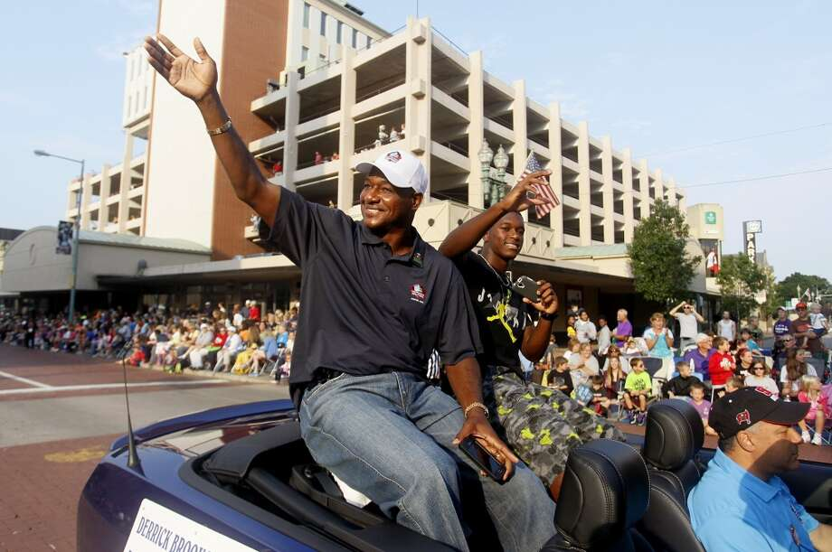 Tampa Bay Buccaneers linebacker Derrick Brooks and son Decalon Brooks, 15, wave to the crowd during the Hall of Fame Timkensteel Grand Parade in downtown Canton, Ohio, on Saturday, Aug 2, 2014. Derrick Brooks is among the 2014 class of inductees to the Pro Football Hall of Fame. Photo: Dirk Shadd, McClatchy-Tribune News Service