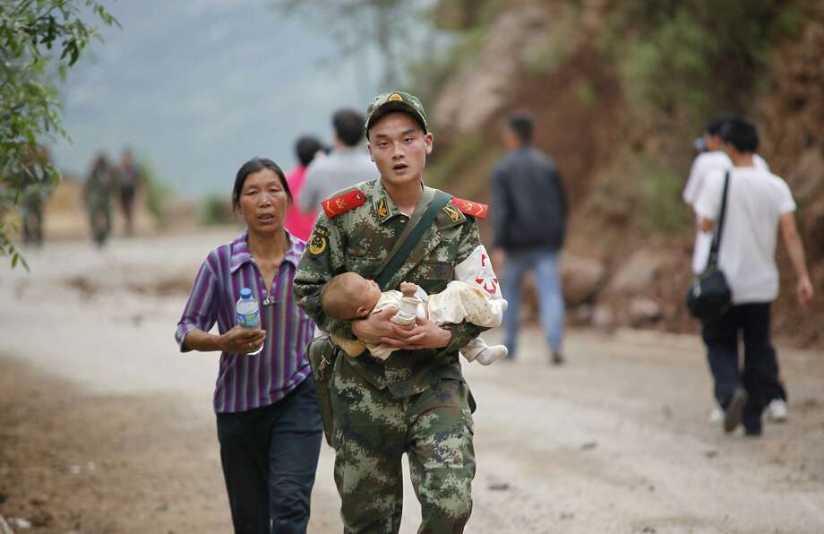 A Chinese rescuer carries a baby after a 6.1-magnitude earthquake struck an area of Ludian county in Yunnan province in southwest China. Tens of thousands have been left homeless. Photo: Str, AFP/Getty Images