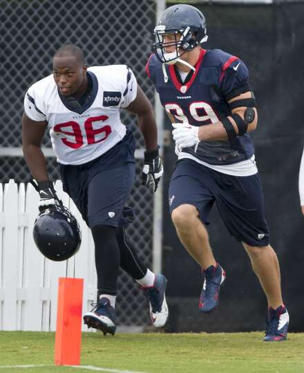 Defensive ends Tim Jamison (96) and  J.J. Watt (99) run onto the practice field.
