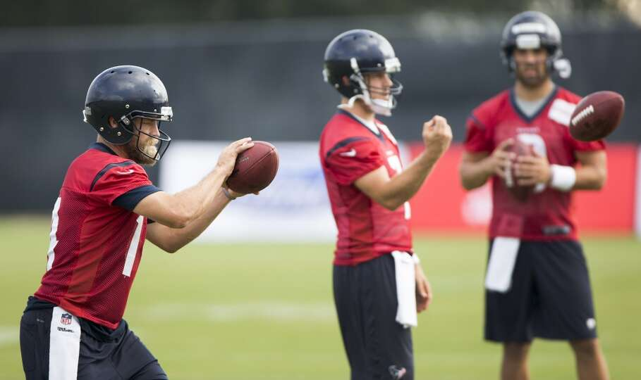 Quarterbacks Ryan Fitzpatrick (14), Case Keenum (7) and Tom Savage (3) warm up before practice.