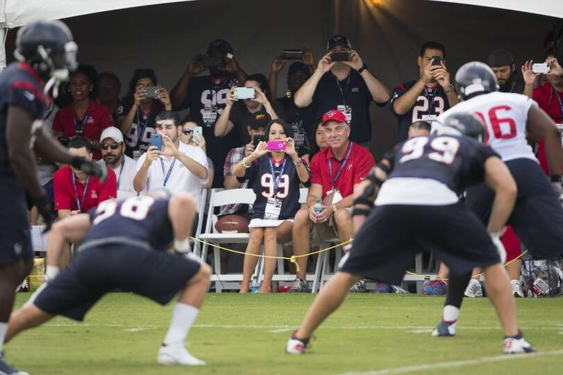 Texans fans take photos from the sidelines.