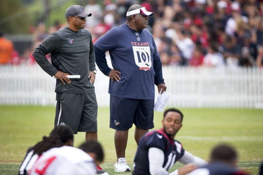 General manager Rick Smith, left, and defensive coordinator Romero Crennel watch the team stretch. Photo: Brett Coomer, Houston Chronicle