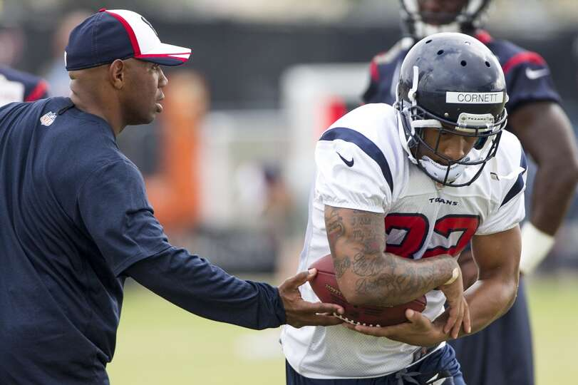 Texans running back Tim Cornett (32) takes a handoff from running backs coach Charles London.