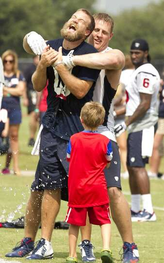 Texans quarterback Ryan Fitzpatrick (14) reacts as he is held by defensive end J.J. Watt and splashe