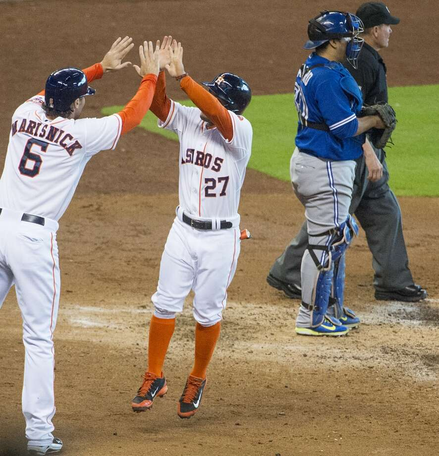 Astros second baseman Jose Altuve (27) celebrates with center fielder Jake Marisnick celebrate after both scored on a double by Chris Carter during the third inning. Photo: Smiley N. Pool, Houston Chronicle