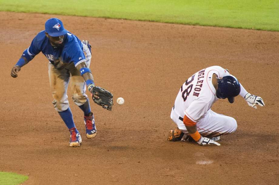 Astros first baseman Jon Singleton slides into second base with a double as the throw gets away from Toronto shortstop Jose Reyes during the fourth inning. Photo: Smiley N. Pool, Houston Chronicle