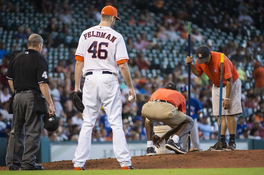 Astros starting pitcher Scott Feldman watches as groundskeepers tend to the mound before the top of the sixth inning. Photo: Smiley N. Pool, Houston Chronicle