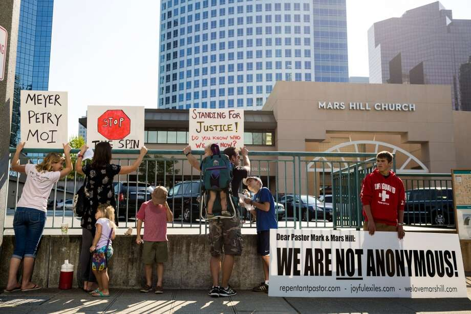 "Toting signs claiming ""We Are Not Anonymous,"" Bailey Strom, right, father Gerd Strom, center, and mother Heidi Strom, second from left - all former members of the Seattle-based Mars Hill Church - made their way from Yakima, Wash., to attend a self-titled ""Peaceful Protest"" Sunday, August 3, 2014, at the church's main site in Bellevue, Wash. The protest came about in regards to Mark Driscoll, pastor of Mars Hill Church, claiming he was confused as to how to reconcile with people who were 'hurt' by his actions because they are 'anonymous.' (Jordan Stead, seattlepi.com) Photo: JORDAN STEAD, SEATTLEPI.COM"