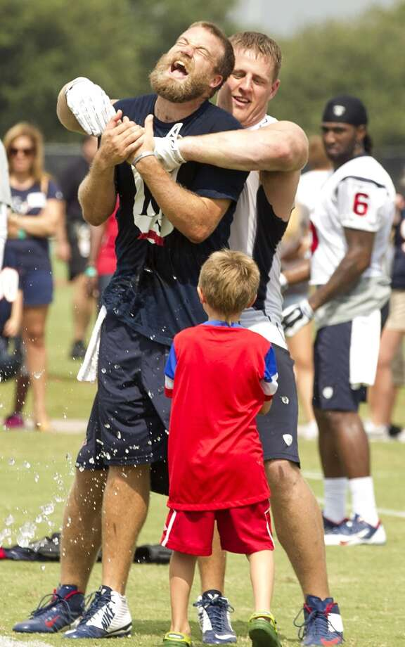 Texans quarterback Ryan Fitzpatrick (14) reacts as he is held by defensive end J.J. Watt and splashed with water by his son, Tate, after practice. Photo: Brett Coomer, Houston Chronicle