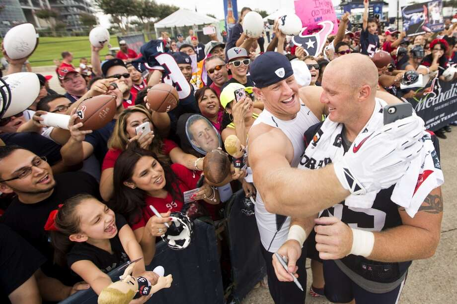 Texans defensive end J.J. Watt, left, clowns around with center Chris Myers trying to take a photo of him and Myers with a fan's phone. Photo: Brett Coomer, Houston Chronicle