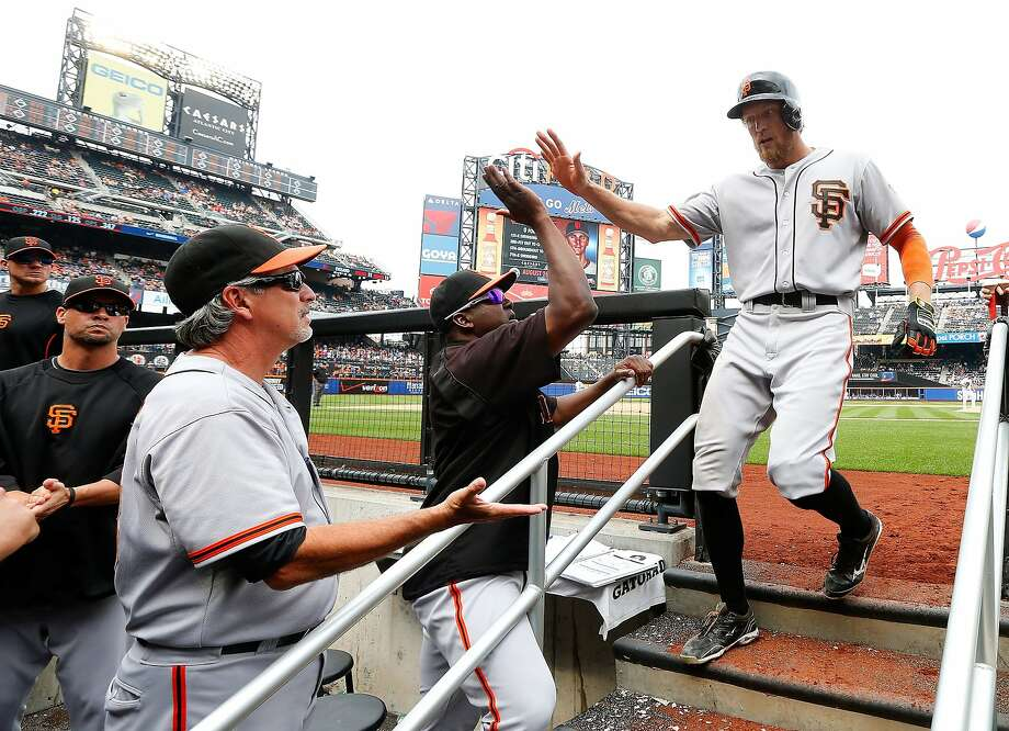 Hunter Pence returns to a dugout welcome from batting coach Hensley Meulens (in black pullover) and bench coach Ron Wotus after hitting his second home run of the game, off Dana Eveland in the ninth inning. Photo: Jim McIsaac, Getty Images