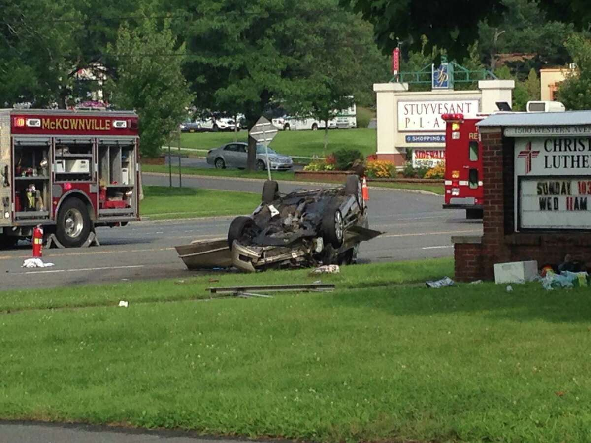 A one-car accident closed part of Western Avenue near Stuyvesant Plaza Sunday, Aug. 3, 2014, in Guilderland, N.Y. The over-turned car came to a rest in front of Christ Lutheran Chruch.