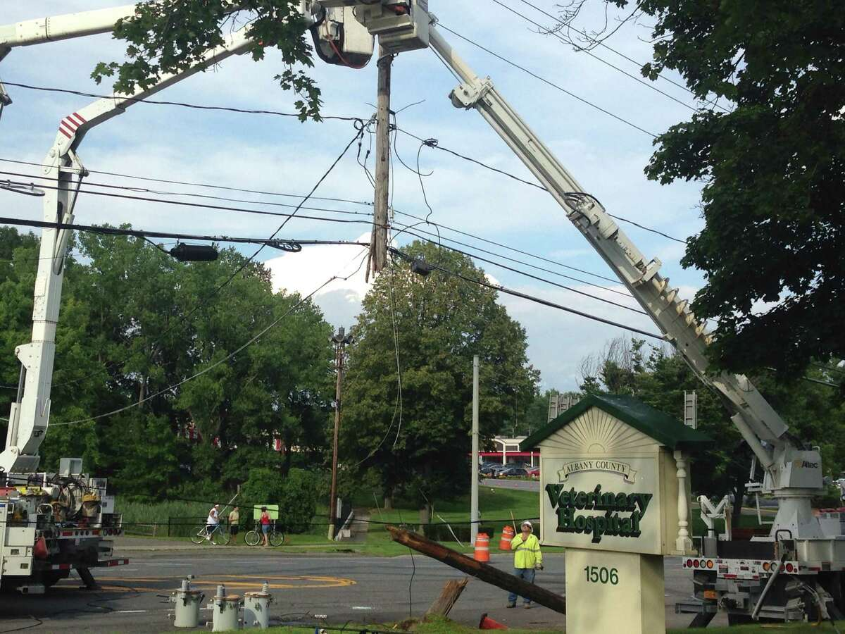 Crews work on a telephone pole that was broken in a one-car accident that closed part of Western Avenue near Stuyvesant Plaza Sunday, Aug. 3, 2014, in Guilderland, N.Y.