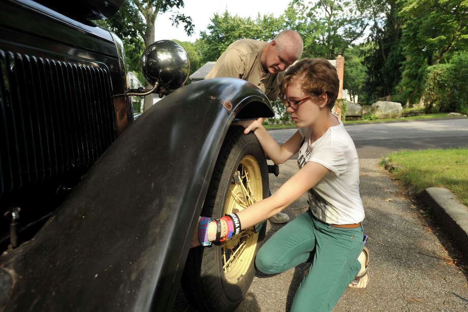 Ken Byrne works on his 1930 Ford Model A's breaking system with his daughter, Maura Byrne, in their driveway in Stamford, Conn., on Sunday, Aug. 3, 2014. Ken originally got the antique to work on as a joint project with his father four years ago and continues his work on it with his daughter as well. Photo: Jason Rearick / Stamford Advocate