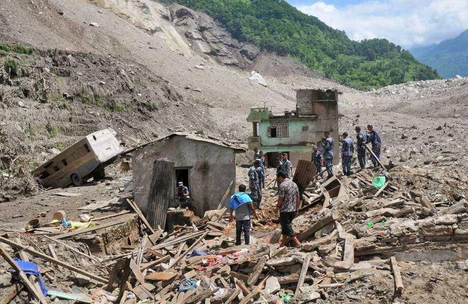 Nepalese security personnel gather for rescue work at the site of a landslide in Sindhupalchowk area, about 120 kilometers (75 miles) east of Katmandu, Nepal, Saturday, Aug. 2, 2014. A massive landslide killed at least eight people and blocked a mountain river in northern Nepal on Saturday, causing the water to form a lake that was threatening to burst and sweep several villages, officials said. (AP Photo/Dinesh Gole) Photo: Dinesh Gole, STR / AP