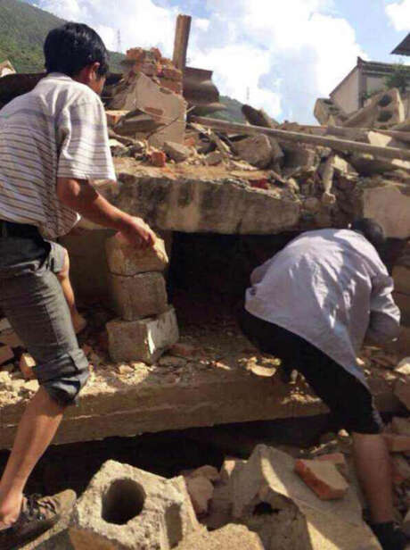 Men search for survivors Sunday after an earthquake turned buildings into rubble in Ludian County in southwest China's Yunnan Province. Photo: Hu Chao, SUB / Xinhua
