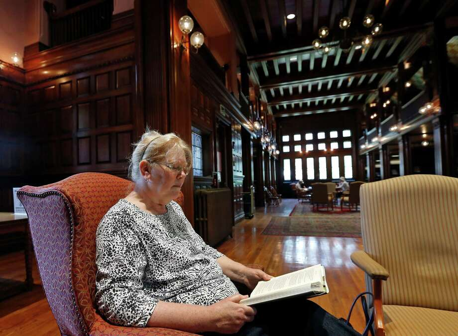 """In this July 7, 2014 photo, Susan McNamara relaxes with a book at her favorite place at the public library in Quincy, Mass. """"Over the years, all I've been able to do, especially as a single parent, is just pay your bills every month,"""" said McNamara, a 62-year-old adjunct professor from the Boston area. """"Anything that's left over is used up when your car breaks down or when the furnace breaks down ... There's never anything left over, ever."""" (AP Photo/Elise Amendola) ORG XMIT: MAEA504 Photo: Elise Amendola / AP"""