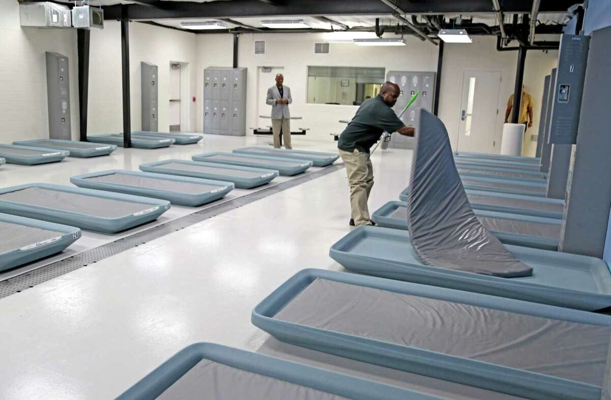 Leonard Kincaid, director, left, watches Douglas Hinton, a recovery specialist, as he cleans a bed at the Houston Center for Sobriety.