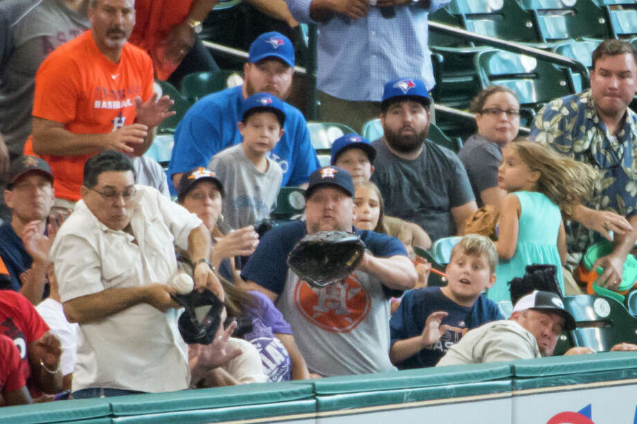 Necessity is the mother of invention as one fan turns his cap into a makeshift glove when trying to catch a foul ball off the bat of Astros outfielder Robbie Grossman during the third inning Sunday. Photo: Smiley N. Pool / © 2014  Smiley N. Pool
