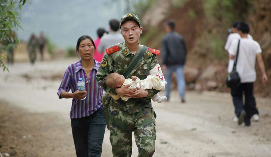A rescuer carries a baby Sunday after a magnitude-6.1 earthquake hit in Zhaotong in southwest China's Yunnan province. The earthquake killed at least 367 and more than 1,800 were injured. Photo: Getty Images / AFP