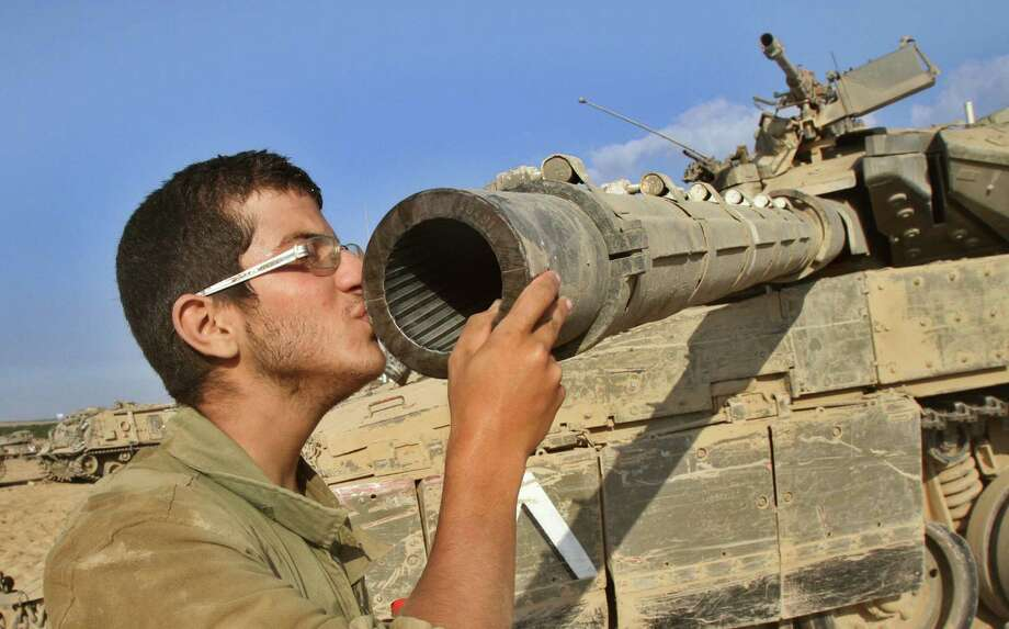 An Israeli soldier kisses his Merkava tank along the border between Israel and the Gaza Strip on Sunday after he pulled out of the strip. An airstrike on a U.N. school killed 10 and wounded 35. Photo: Gil Cohen Magen / Getty Images / AFP