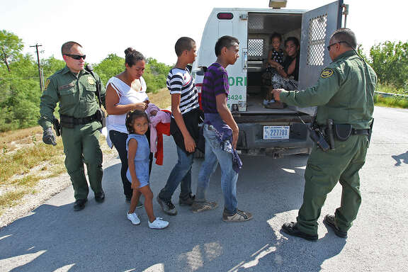 """U.S. Border Patrol agents load  a group of adult and minor immigrants onto a van near Anzalduas Park, southwest of McAllen, on June 11. U.S. Rep. Henry Cuellar warned agencies dealing with the border influx will have to make """"some painful choices"""" since Congress didn't pass a bill to send them aid before it went to recess."""