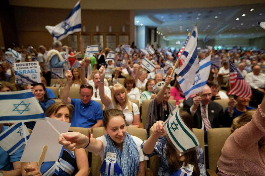 At left, Ellen Taer and her daughters, Nicki, 20, and Jennie, 18, wave Israeli flags at a rally in support of Israel on Sunday. Photo: Johnny Hanson, Staff / © 2014  Houston Chronicle