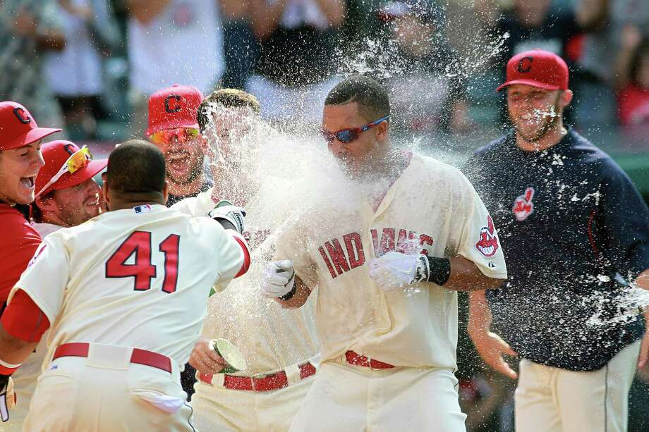 Michael Brantley (center) is hit with water by his Indians teammates after his game-winning homer. Photo: Aaron Josefczyk / Associated Press / FR171101 AP