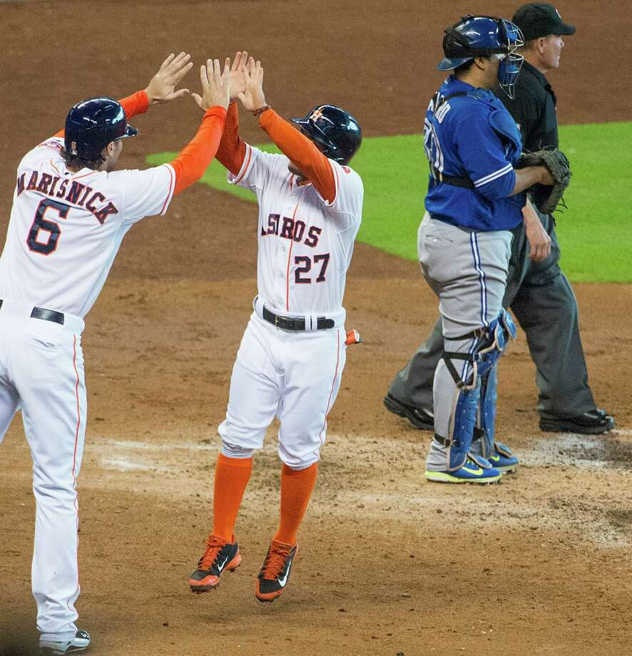 Newest Astro Jake Marisnick, left, and the more-established Jose Altuve come together after scoring on a single by Chris Carter during the third inning Sunday. The single gave Carter the club lead in RBIs with 53, two ahead of George Springer. Photo: Smiley N. Pool / © 2014  Smiley N. Pool