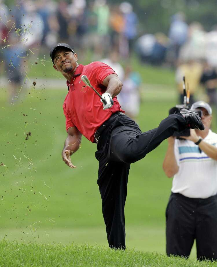 Tiger Woods grimaces after an awkward follow through on a shot at the lip of a fairway bunker. Photo: Mark Duncan / Associated Press / AP