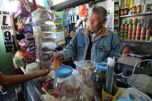 "Antonio Neira Lopez, 83, sells to a customer at his store in the Agua Nueva ejido south of Saltillo, Coahuila, Mexico, Tuesday, Feb. 18, 2014. The state of Coahuila owes nearly $3 billion in debt, an amount that equals its yearly budget. Most blame the past government of Governor Humberto Moreira for the debt. ItÕs been dubbed  ""megadeuda,"" by the Mexican press. Photo: Jerry Lara, San Antonio Express-News / ©2013 San Antonio Express-News"