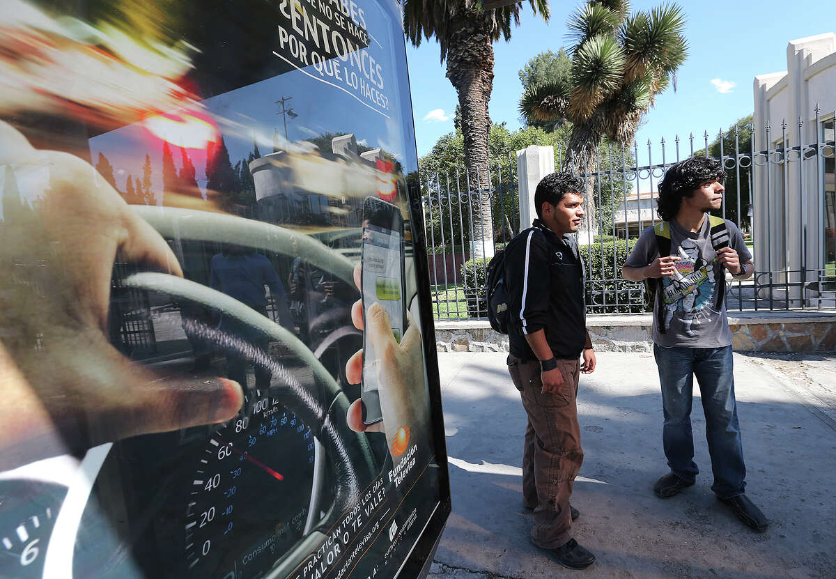 Universidad Autonoma de Coahuila engineer students Mario Galindo, 19, left, and Abraham Fabian, 19, wait for the bus in Saltillo, Mexico, Wednesday, Feb. 19, 2014. The state is under an almost $3 billion debt incurred by the former administration of Governor Humberto Moreira.