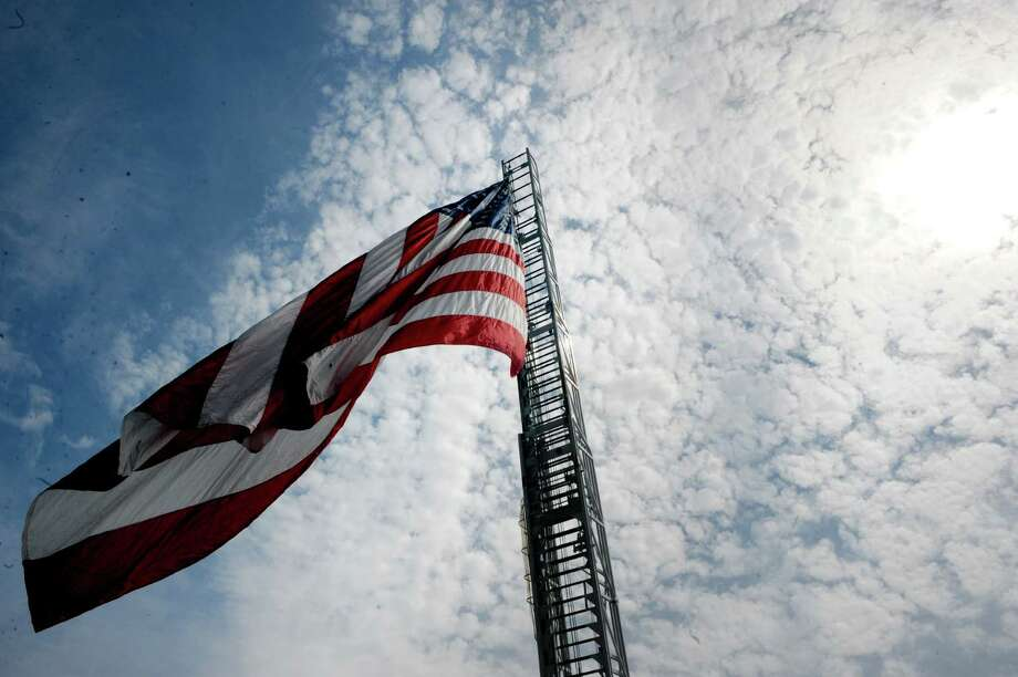 """A giant United States Flag hangs over Broad Street during the 20th annual Turning Point Parade on Sunday Aug. 3, 2014 in Schuylerville, N.Y. 20th annual Turning Point Parade on Sunday, Aug. 3, 2014 in Schuylerville, N.Y. The event marks the 1777 surrender of the British, often considered the American Revolutionary War's """"Turning Point."""" (Michael P. Farrell/Times Union Photo: Michael P. Farrell / 00027929A"""