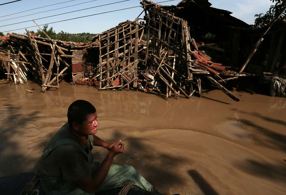 Rescue workers patrol in a boat near a damaged house, as they look for people in the flooded streets in the town of Misia, some 175 km north from the capital Sofia, Sunday, Aug. 03,  2014.  The Skat River has burst its banks in northwestern Bulgaria following weeks of torrential rain, killing one person and forcing authorities to evacuate hundreds. Hundreds of properties have been swamped on Sunday in Misia, the worst-hit city. The situation in the area remains critical. Heavy rain has hit this Balkan country for weeks, with some 15 people killed in flood-related incidents. (AP Photo/Valentina Petrova) Photo: Valentina Petrova, Associated Press